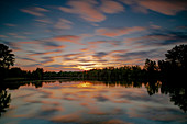 Bavaria, Germany, the Langwieder lake district in the evening mood with reflection of the evening cloud sky in the water surface. Local recreation area in western Munich, Europe, Munich, Upper Bavaria