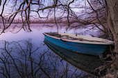 Small rowing boat lies on the banks of the Langwiedersee in the morning mood. Langwiedersee, Munich, Upper Bavaria, Bavaria, Germany, Europe