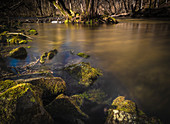 Long exposure of the Würm river near Gauting. Stones and roots are in the worm. Gauting, Starnberg, Upper Bavaria, Bavaria, Germany, Europe