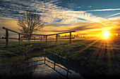 Small brook with bridge and rising sun on a field in the west of Munich. Munich, Upper Bavaria, Bavaria, Germany, Europe