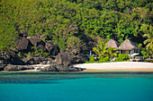 Dream beach and palm trees with small huts of a beach resort, Naviti Island, Fiji