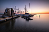 View of sailing boats on jetty on Lake Ammer at sunset, Bavaria, Germany, Europe