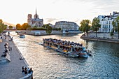 France, Paris, area listed as World Heritage by UNESCO, Bateau Mouche passing Saint Louis Island on the right, Notre Dame Cathedral on the Ile de la Cite and the quayside of La Tournelle