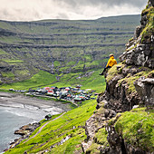 The hiker is admiring the little village of Tjornuvik, Streymoy island, Faroe Islands, Denmark, Europe