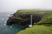 Hiker admiring the Mulafossur waterfall and the village of Gasadalur, Vagar island, Faroe Islands, Denmark, Europe