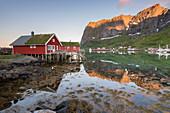 Das Fischerdorf und die Berge spiegeln sich im Wasser während der Mitternachtssonne, Reine, Provinz Nordland, Lofoten, Nordnorwegen, Europa