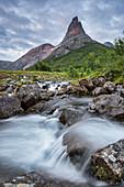 Waterfall in front of Stetinden mountain peak illuminated by midnight sun, Tysfjord, Norway, Europe