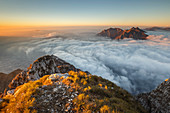 Sunrise on Lecco mountains (Corni di Canzo, Rai, Moregallo) wrapped of clouds from the top of Coltignone mount, Piani dei Resinelli, Lecco province, Lombardy, Italy, Europe