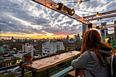 Woman watching the sunset from a terrace in Palermo neighbourhood, Buenos Aires, Argentina, South America