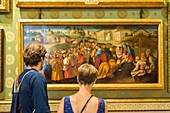 Italy, Tuscany, Florence, historical center listed as World Heritage by UNESCO, couple looking at the chart the Adoration of the Magi by Jacopo Pontormo exposed to the Palatine Gallery in the Pitti Palace