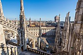 Italy, Lombardy, Milan, the arrows and statues of Duomo seen since the terrace situated on the roof of the cathedral with a view of the Palazzo Reale museum, the church San Gottardo in Corte or San Gottardo a Palazzo and the tower Velasca