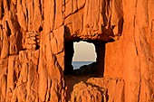 Italy, Sardinia, Tyrrhenian Sea, Arbatax, wild rocky coast, beach Rocce Rosse, antique red porphyry, the massive red rock layer solei, leaving a hole in the rock appear on the horizon a Cargot