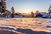 Snowy winter landscape with coniferous forest at sunrise, Himmelberg, Carinthia, Austria