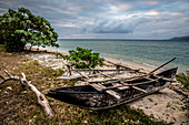 Dugout boat lies on a beach, Efate, Vanuatu, South Pacific, Oceania