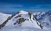 Skitourengeher im Gebirge der Kitzbüheler Alpen beim Aufstieg zum Gipfel des Tristkopf in der Sonne, Winter in Tirol, Österreich