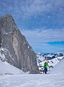 Man on ski tour at Ellmauer Tor in the Wilder Kaiser Mountains