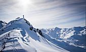 Skifahrer am Gipfelgrat kurz vor der Abfahrt im Tiefschnee in Hochfügen, Winter in Tirol, Österreich