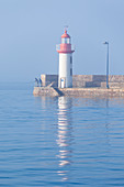 Angler in the morning at the Eruqy lighthouse - harbor entrance, at high tide.