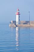 Angler morgens am Leuchtturm von Eruqy, Hafeneinfahrt, bei hoher Flut, Cote d Armor, Bretagne, Frankreich