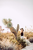 Woman stands next to Joshua Tree in Joshua Tree National Park, Joshua Tree, Los Angeles, California, USA, North America