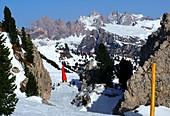 Skifahren über Wolkenstein mit Geislergruppe im Hintergrund, Grödnertal, Dolomiten, Südtirol, Italien