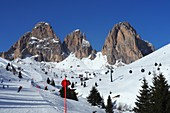Ski under the Langkofel over Campitello, skier, ski slope, rocks, Dolomites, Trentino in winter, Italy