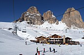 Ski under the Langkofel over Campitello, skier, ski slope, rock, ski hut, Dolomites, Trentino in winter, Italy