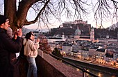 Evening view from Kapuzinerberg, tourists, city view, panorama, branches, lights, river, castle, cathedral, reflections, Stadthäuserm Salzburg in winter, Austria