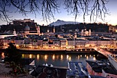 Evening view from Kapuzinerberg, city view, panorama, branches, lights, river, castle, cathedral, reflections, Stadthäuserm Salzburg in winter, Austria