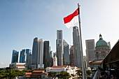 Singapore, Republic of Singapore, Asia - The red and white national flag waves in front of the city skyline of the central business district with the skyscrapers in Marina Bay and Raffles Place.