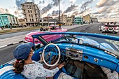 A classic blue American muscle car riding alongside some classic pink cars , Havana, Cuba