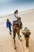 Woman and guide in a dromedary ride in the desert. Douz, Tunisia, Africa.