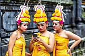 Young Balinese Hindu Females Looking At A Mobile Phone (Cellphone) At The Batara Turun Kabeh Ceremony, Besakih Temple, Bali, Indonesia.