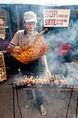Indonesischer Mann bereitet Fleisch auf der Straße zu, Jakarta, Indonesien