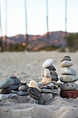 Piled stones on the beach in the evening light with a view of the Santa Ynez Mountains in Santa Barbara, California, USA.