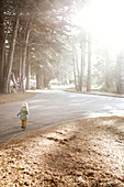 Child runs down a street near Big Sur, California, USA.