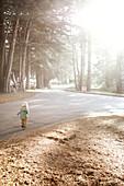 Kind läuft eine Strasse entlang bei von Big Sur, Kalifornien, USA.