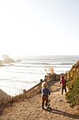 Children run along a walking path in Big Sur, California, USA.