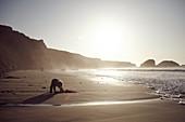 Kleines Kind buddelt im Abendlicht am Strand von Big Sur, Kalifornien, USA.