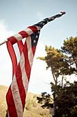 Amerikanische Flagge im Abendlicht auf einem Parkplatz bei Big Sur am Highway 1, Kalifornien, USA.