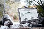 Information sign for hikers to protect rainbow trout on the Big Sur River in Pfeiffer Big Sur State Park, California, USA.