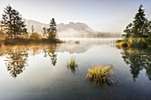 Sunrise at the Barmsee with a view towards the Karwendel massif, Bavaria, Germany.