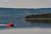 Junge Frau in einem Ruderboot, Orsjön, Tomterna, Västernorrbotten, Schweden