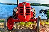 Ein uralter roter Traktor am See, Volvo, Orsjön, Tomterna, Västernorrland, Schweden