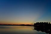 Späte Dämmerung mit Lichtstrahlen hinter einem Hügel, Orsjön, Tomterna, Västernorrland, Schweden
