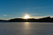 Setting sun over a frozen lake in winter, Bolmsjön, Halland, Sweden
