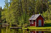 Ein versteckter Badeplatz mit Steg und Hütte an einem See in Stengårdshult, Schweden