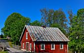 Ein rotes Schwedenhaus am Fluss in der Nähe von  Stengardshult, Schweden