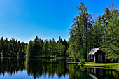 A small hut with a jetty by the lake in the middle of the forest near Stengårdshult, Sweden