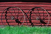 Zwei Metallräder lehnen an einer roten Holzhütte, Hundsjön, bei Boden, Norrbottens Län, Schweden